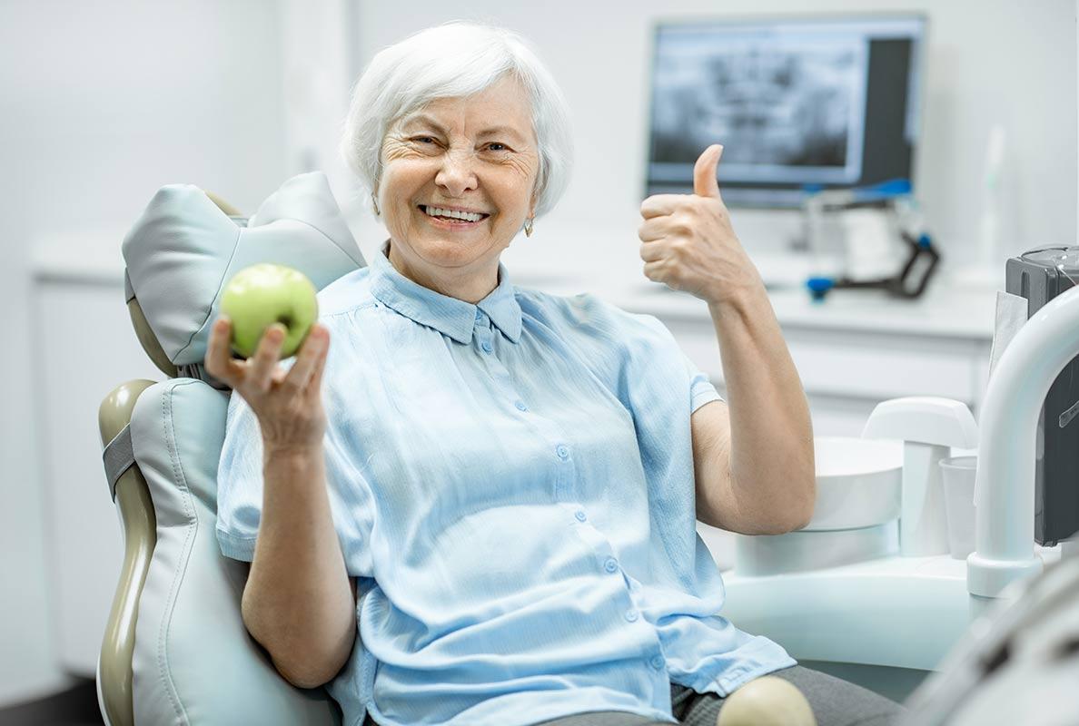 Foto mit einer älteren Fraus mit einem grünen Apfel in ihrer rechten Hand - Zahnarztpraxis Osnabrück - Dr. med. dent. Michael Löw