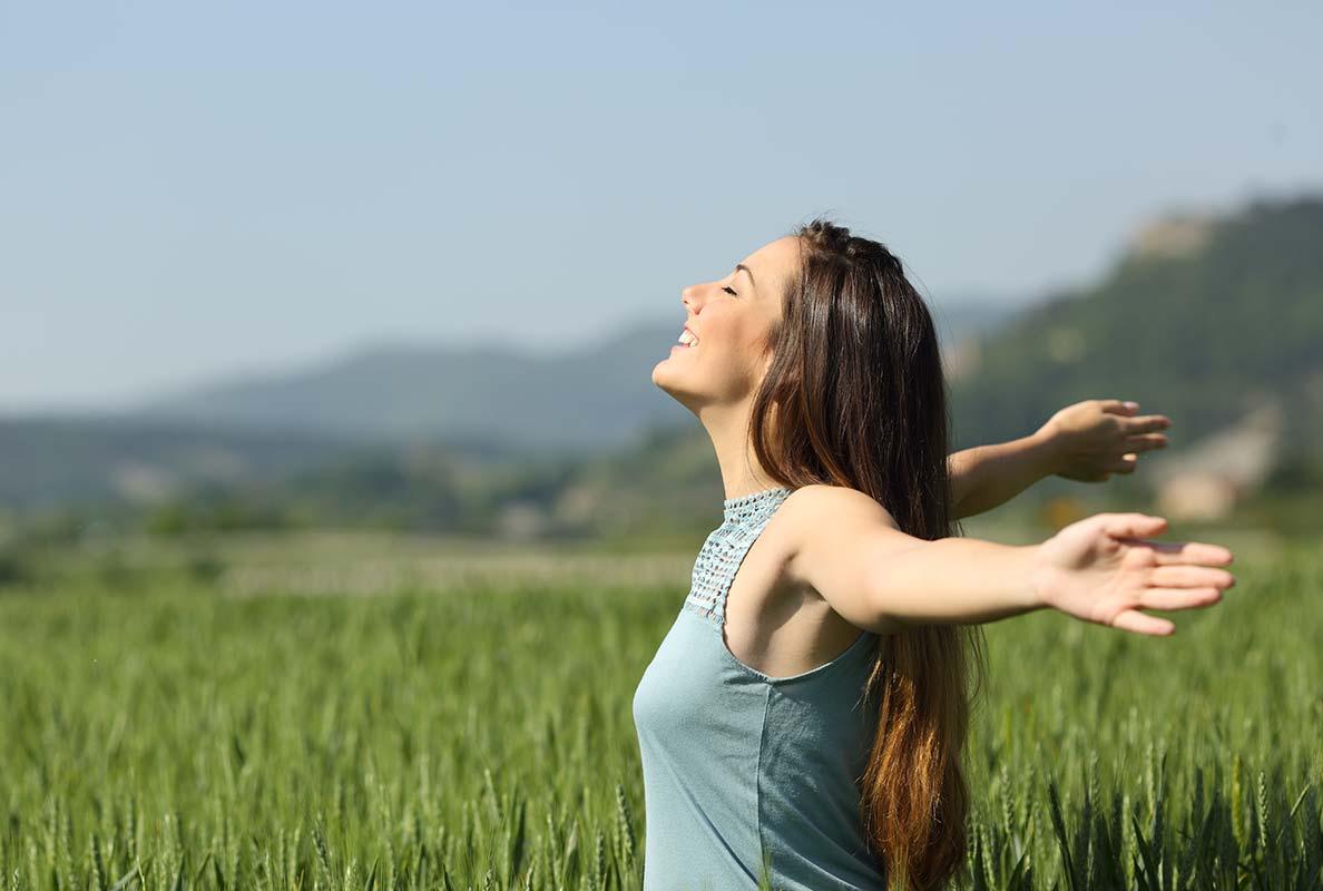 Frau in der Natur, im grünen Feld, die Sonne scheint und die Frau breitet ihre Arme aus.